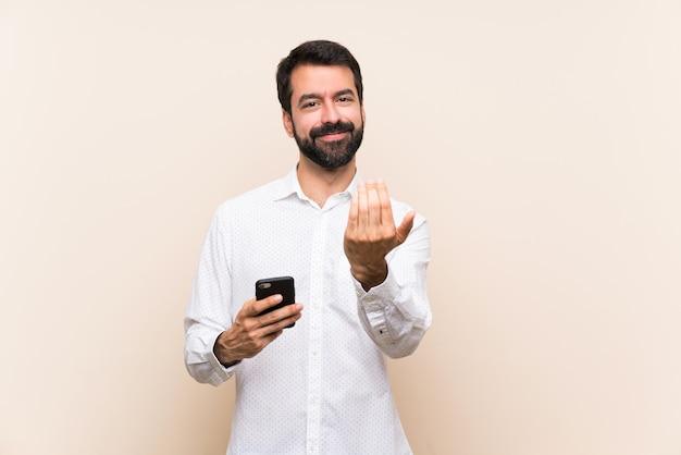 Hombre joven con barba sosteniendo un móvil invitando a venir con la mano. feliz de que hayas venido