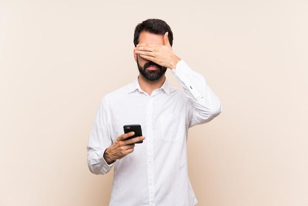 Hombre joven con barba sosteniendo un móvil que cubre los ojos con las manos. no quiero ver algo