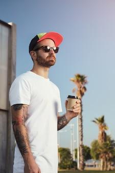 Hombre joven con barba y tatuajes en camiseta blanca sin etiqueta con una taza de café contra el cielo azul y palmeras