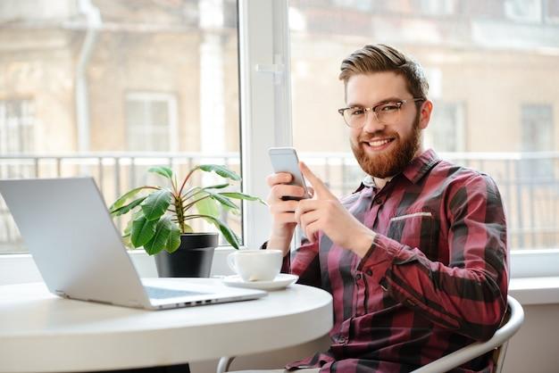 Hombre joven barbudo feliz que usa el teléfono móvil y la computadora portátil.