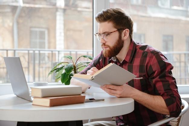 Hombre joven barbudo pensativo que lee los libros mientras que usa la computadora portátil