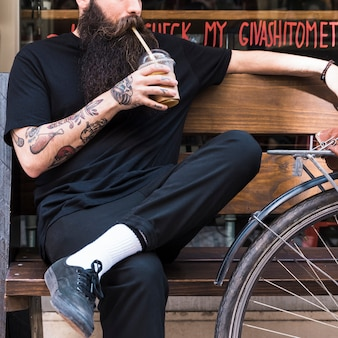 Hombre joven barbudo que bebe el batido de chocolate sentado en el banco