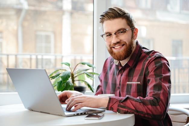 Hombre joven barbudo que usa la computadora portátil.
