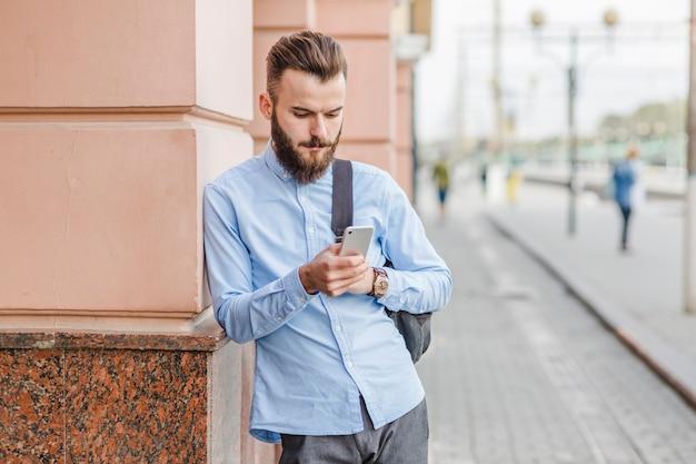 Hombre joven barbudo que usa el teléfono móvil en el aire libre