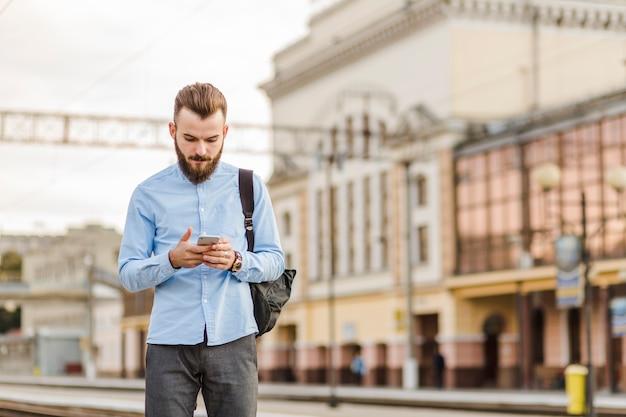 Hombre joven barbudo que usa el teléfono móvil en la estación de tren