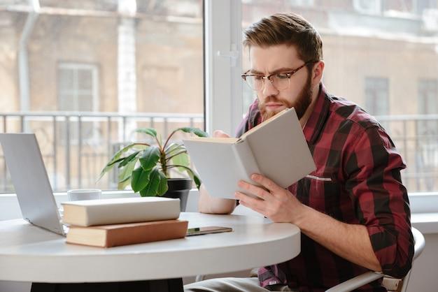 Hombre joven barbudo serio hermoso que lee los libros mientras que usa la computadora portátil