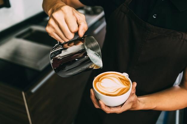Hombre joven barista vertiendo leche caliente en café negro espresso caliente para hacer arte latte