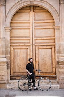 Hombre joven con bicicleta de pie cerca de la puerta cerrada de la vendimia