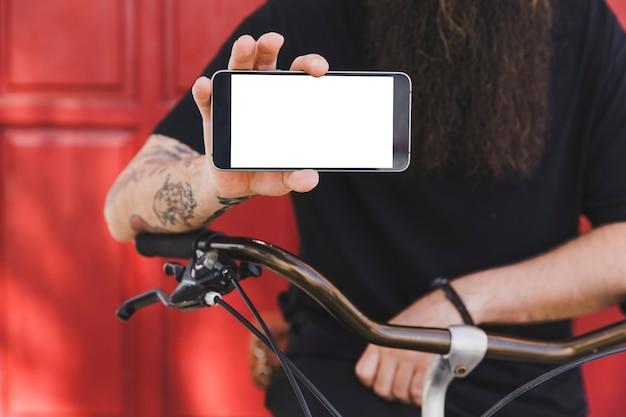 Hombre joven con la bicicleta que muestra la pantalla del teléfono móvil