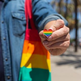 Hombre joven con bolsa reutilizable de arco iris y insignia en forma de corazón lgbtq durante el mes del orgullo. libertad, diversidad, aceptación, concepto lgbt