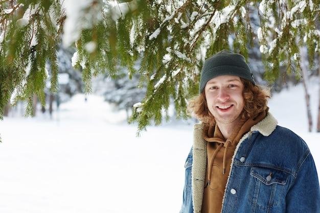 Hombre joven en bosque de invierno