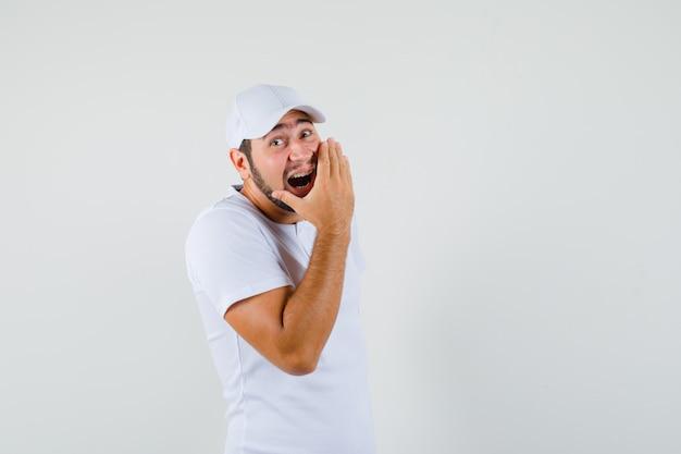 Hombre joven bostezando en la boca con la mano en la camiseta blanca y con aspecto cansado