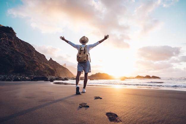 Hombre joven con los brazos extendidos junto al mar al amanecer disfrutando de la libertad y la vida, la gente viaja concepto de bienestar