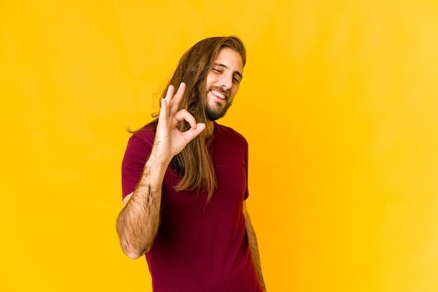 Hombre joven con cabello largo mira alegre y confiado mostrando gesto ok