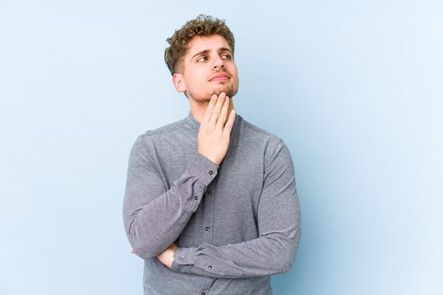 Hombre joven de cabello rizado rubio aislado contemplando, planeando una estrategia, pensando en el camino de un negocio
