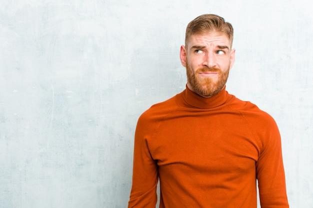 Hombre joven de cabeza roja con cuello de tortuga que parece confundido y confundido, preguntándose o tratando de resolver un problema o pensando contra la pared de concreto