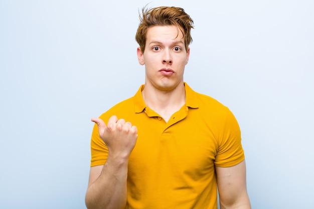 Hombre joven de cabeza roja que mira asombrado con incredulidad, apuntando a un objeto a un lado y diciendo wow, increíble contra la pared azul