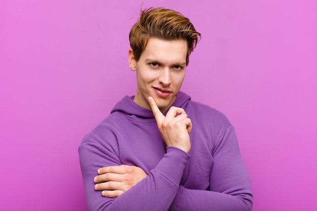 Hombre joven de cabeza roja que parece feliz y sonriente con la mano en la barbilla, preguntándose o haciendo una pregunta, comparando opciones contra la pared púrpura