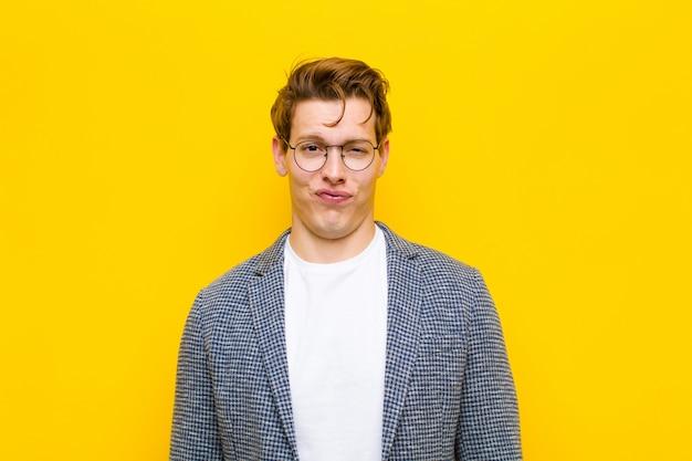 Hombre joven de cabeza roja que parece tonto y divertido con una expresión tonta con los ojos cruzados bromeando y bromeando sobre fondo naranja