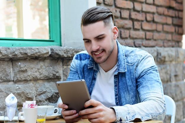 Hombre joven en café de la cafetería usando una tableta.