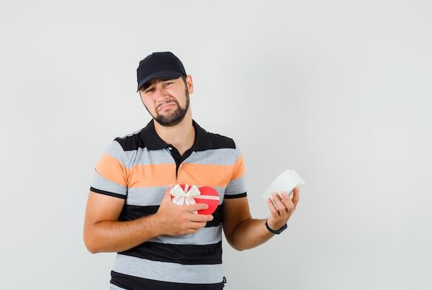 Hombre joven con caja presente vacía en camiseta, gorra y mirando abatido. vista frontal.
