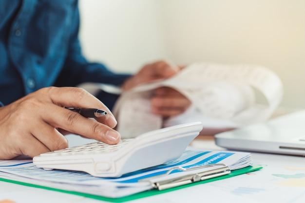 Hombre joven con calculadora y calcular facturas en la oficina en casa concepto de finanzas.