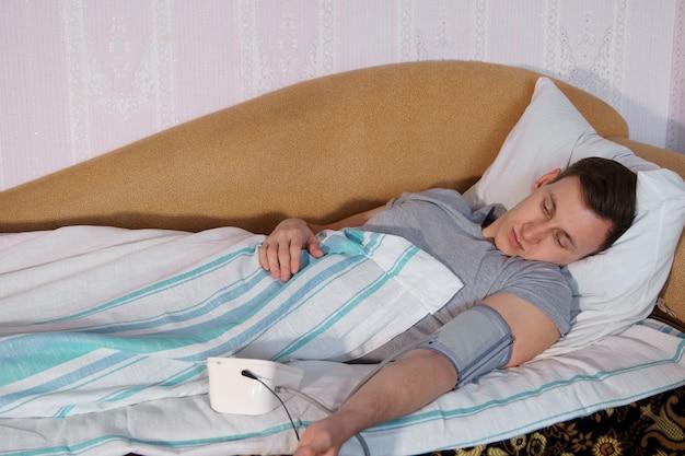 Hombre joven en la cama mide la presión con un tonómetro electrónico.