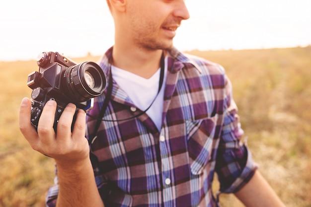 Hombre joven con cámara de fotos retro hipster al aire libre estilo de vida