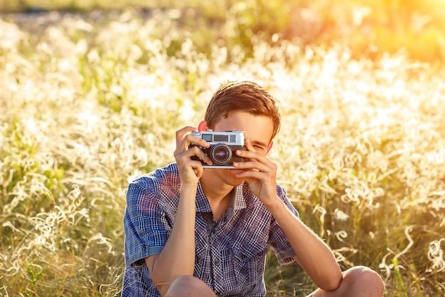 Un hombre joven con una cámara que toma imágenes del fondo natural rayos de sol teñidos