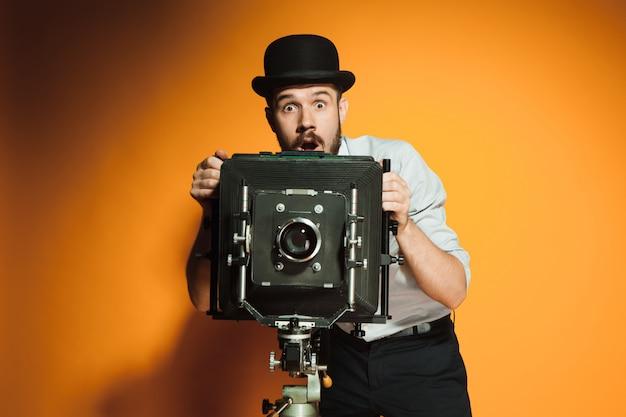 Hombre joven con cámara retro