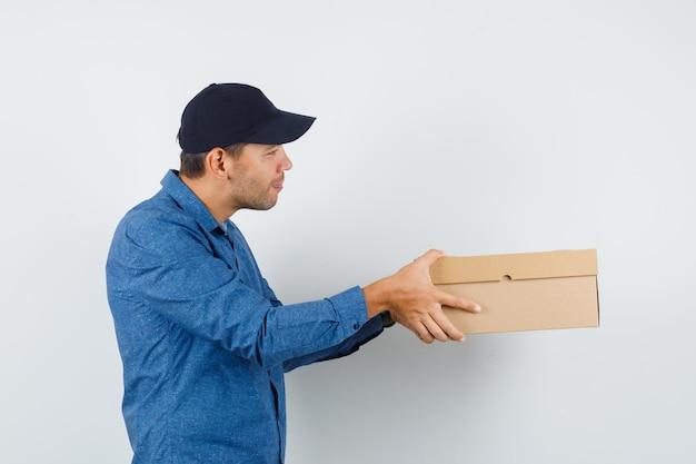 Hombre joven con camisa azul, gorra entregando caja de cartón y mirando alegre.