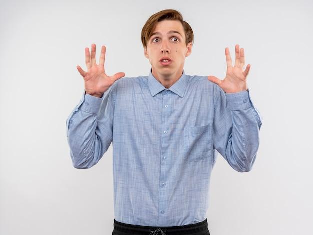 Hombre joven con camisa azul levantando las manos en señal de rendición teniendo miedo de pie sobre la pared blanca