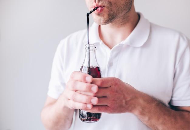 Hombre joven en la camisa blanca aislada. corte el retrato de vista del chico que sostiene la botella con coca cola dentro y beba a través de paja plástica.