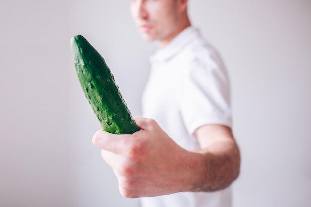 Hombre joven en la camisa blanca aislada sobre la pared. guy mira el pepino largo en la mano. vista de corte borrosa pared desenfocada.