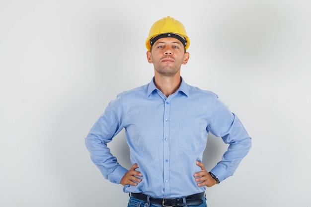 Hombre joven en camisa, casco, jeans de pie con las manos en la cintura y mirando confiado