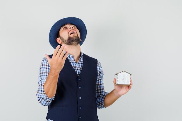 Hombre joven en camisa, chaleco, sombrero con modelo de casa, mirando hacia arriba y mirando esperanzado, vista frontal.