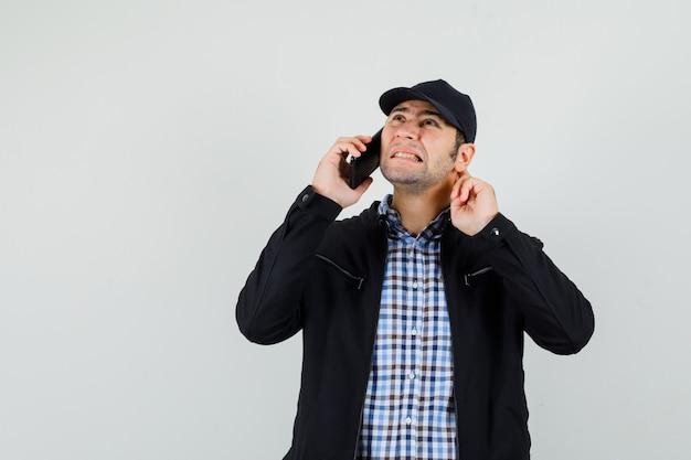Hombre joven en camisa, chaqueta, gorra oyendo mal mientras habla por teléfono móvil