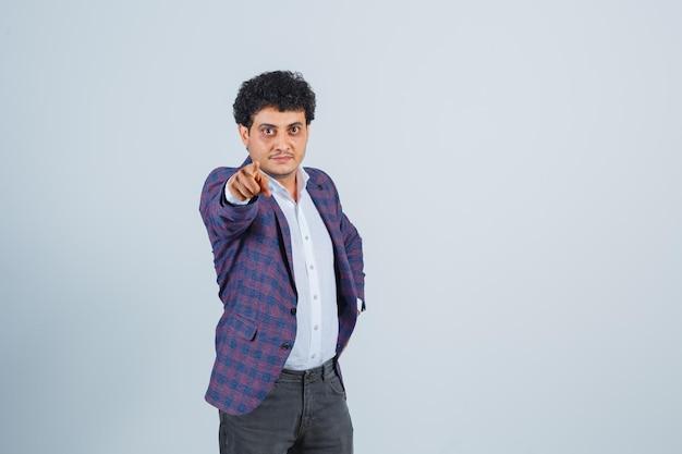 Hombre joven en camisa, chaqueta, pantalón apuntando a la cámara y mirando confiado, vista frontal.