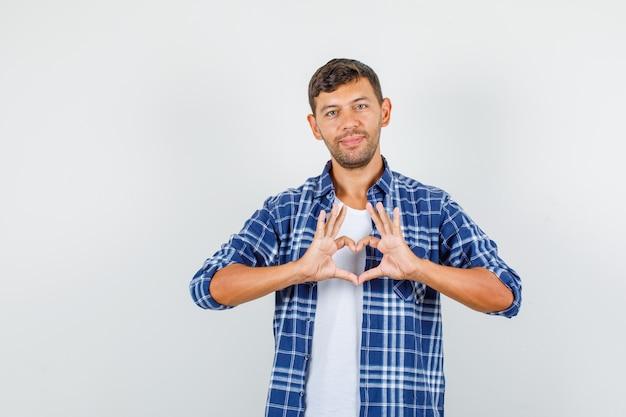 Hombre joven en camisa haciendo gesto con forma de corazón y sonriendo, vista frontal.