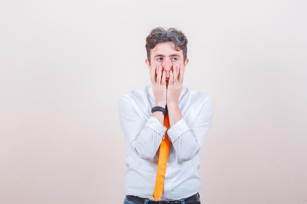 Hombre joven en camisa, jeans tomados de la mano en la cara y mirando angustiado