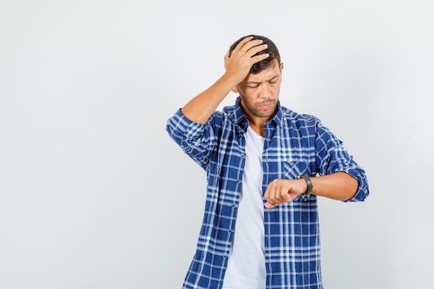 Hombre joven en camisa mirando el reloj con la mano en la cabeza y mirando preocupado, vista frontal.