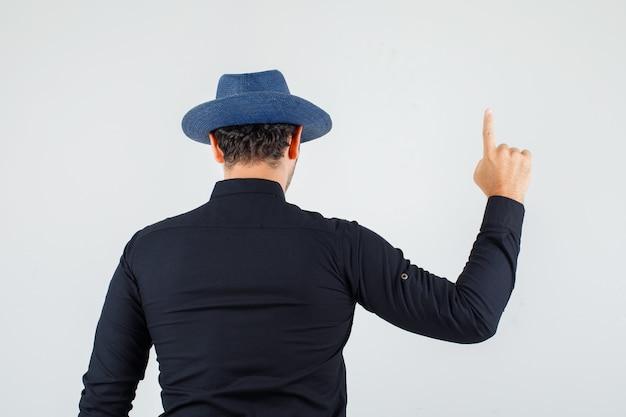 Hombre joven con camisa negra, sombrero apuntando hacia arriba y mirando confiado