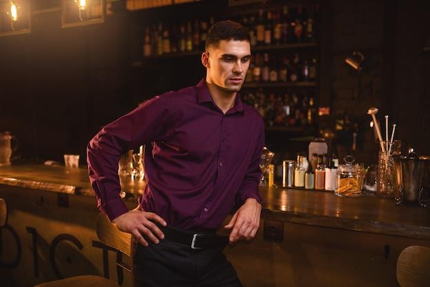 Hombre joven en camisa de pie en la barra del bar