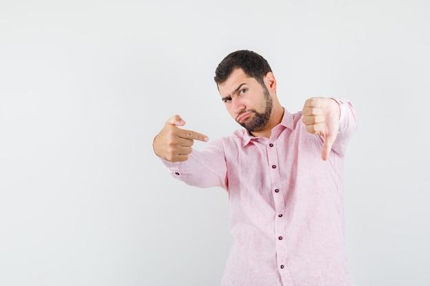 Hombre joven con camisa rosa apuntando a su pulgar hacia abajo y mirando decepcionado