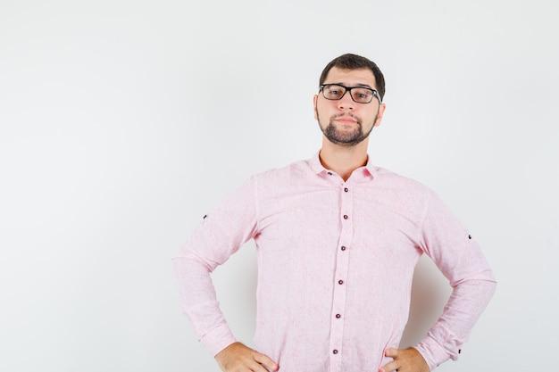 Hombre joven en camisa rosa de pie con las manos en la cintura y mirando confiado