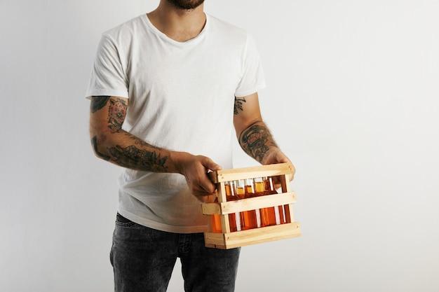 Hombre joven en camiseta de algodón blanco con tatuajes sosteniendo una caja de cerveza artesanal aislado en blanco