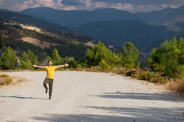 Hombre joven en camiseta amarilla de pie con las manos levantadas en la carretera de una montaña y disfrutando de la vista del valle.