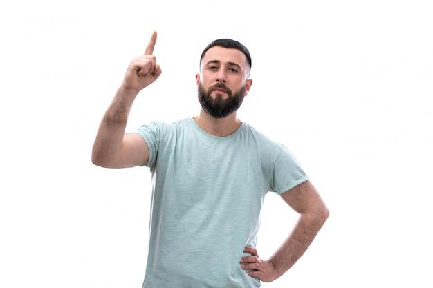 Hombre joven en camiseta azul con barba posando apuntando con su dedo