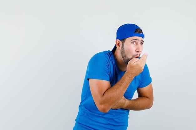 Hombre joven en camiseta azul y gorra silbando aguantando la respiración
