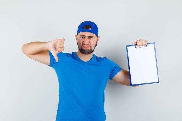 Hombre joven en camiseta azul y gorra sosteniendo el portapapeles con el pulgar hacia abajo y mirando disgustado